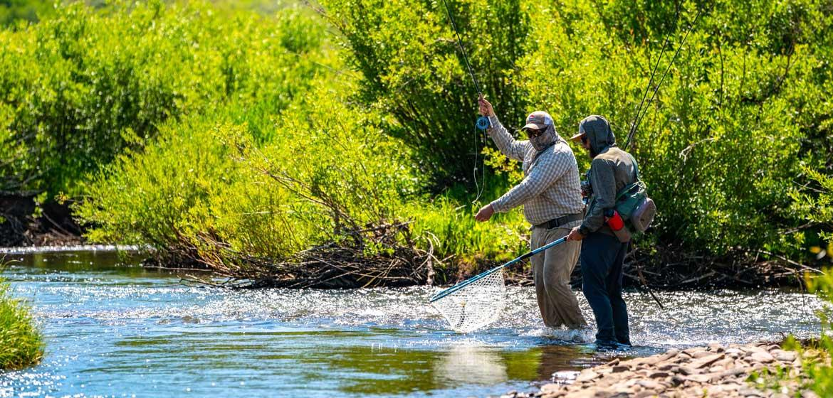 Two people fly fishing on a river in Utah