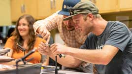 An instructor helping a student in a beginner fly tying class at Fishwest in Sandy, UT