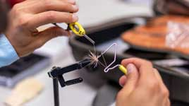 A fly tying class attendee tying a fly using tools and a vice