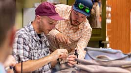 An instructor helping a student tie a fly in an intermediate fly tying class at Fishwest in Sandy, UT