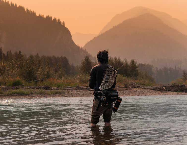 Dana Harrison fly fishing at sunset with smoky mountains in the background