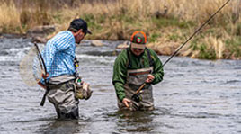 fly fishing guide puts net away as customer smiles at the catch he holds